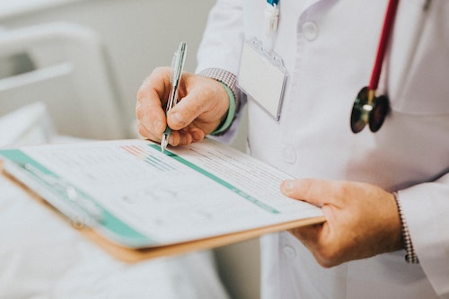 doctor-writing-medical-report